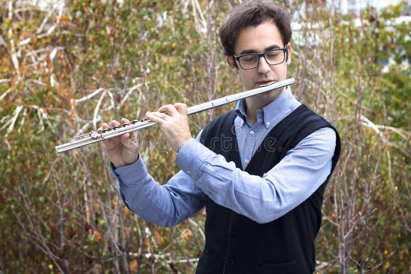 使用一位男性的长笛演奏家户外 免版税库存图片