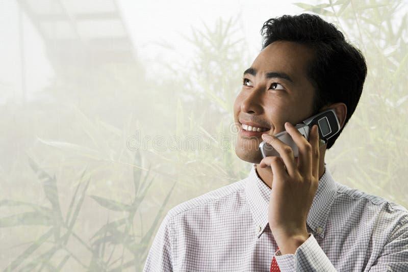 使用一台手机的年轻商人 免版税图库摄影