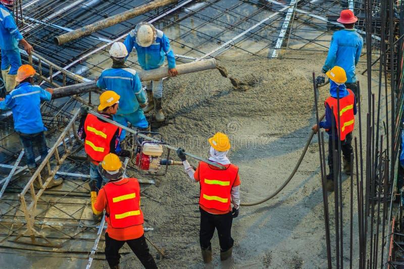 使用一台混凝土振动器汽油发动机的建筑工人在建造场所键入变紧密在r的液体混凝土 库存图片