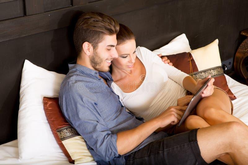 使用一台片剂个人计算机的年轻夫妇在一个亚洲旅馆客房 免版税库存照片