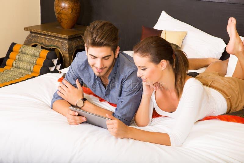 使用一台片剂个人计算机的年轻夫妇在一个亚洲旅馆客房 免版税库存图片