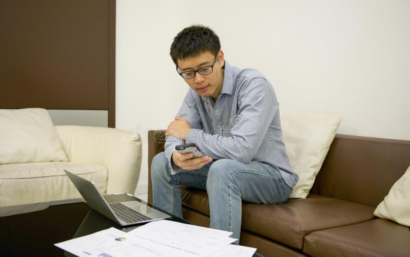 使用一台膝上型计算机的亚洲商人在客厅在晚上 库存图片
