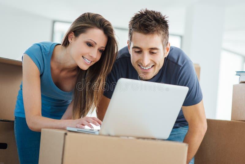 使用一台膝上型计算机的夫妇在他们的新房里 库存照片