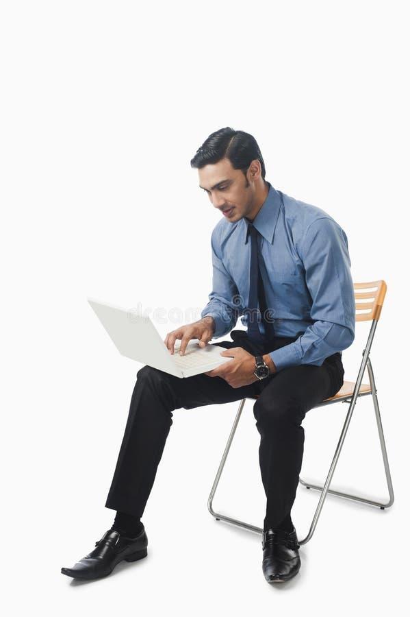 使用一台膝上型计算机的孟加拉商人在椅子 免版税图库摄影