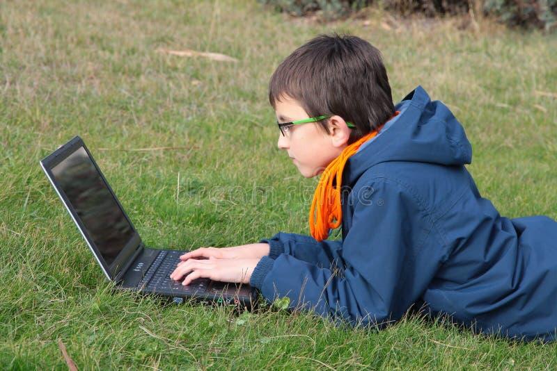 使用一台膝上型计算机的孩子在草 免版税库存图片