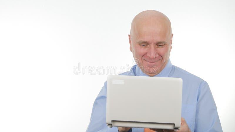 使用一台膝上型计算机的愉快的商人图象微笑通信的 库存图片