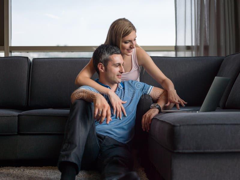 使用一台膝上型计算机的有吸引力的夫妇在长沙发 免版税库存图片