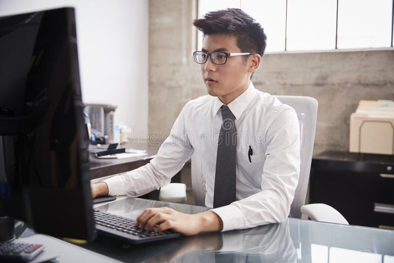 使用一台计算机的年轻亚洲商人在办公桌 库存图片
