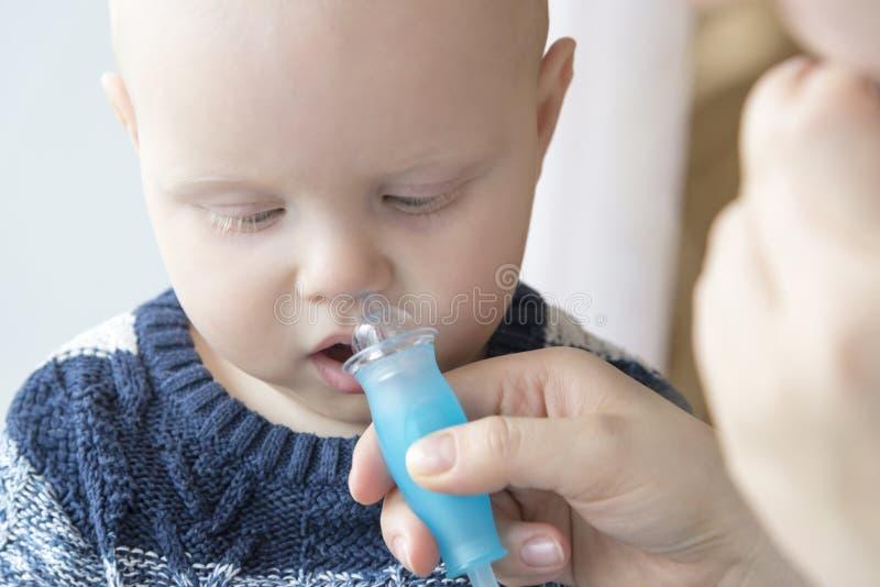 使用一台鼻吸气器,妈妈清洗婴孩的鼻子 免版税库存照片