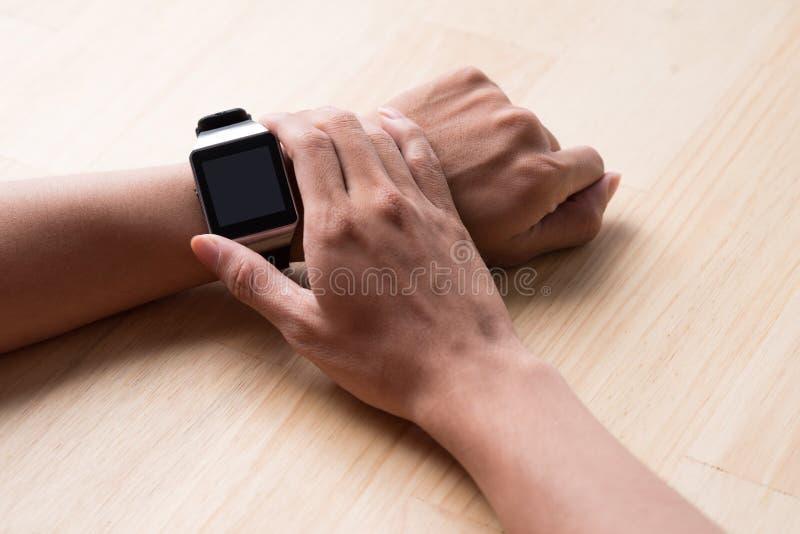 使用一块现代巧妙的手表,关闭男性手 免版税库存照片