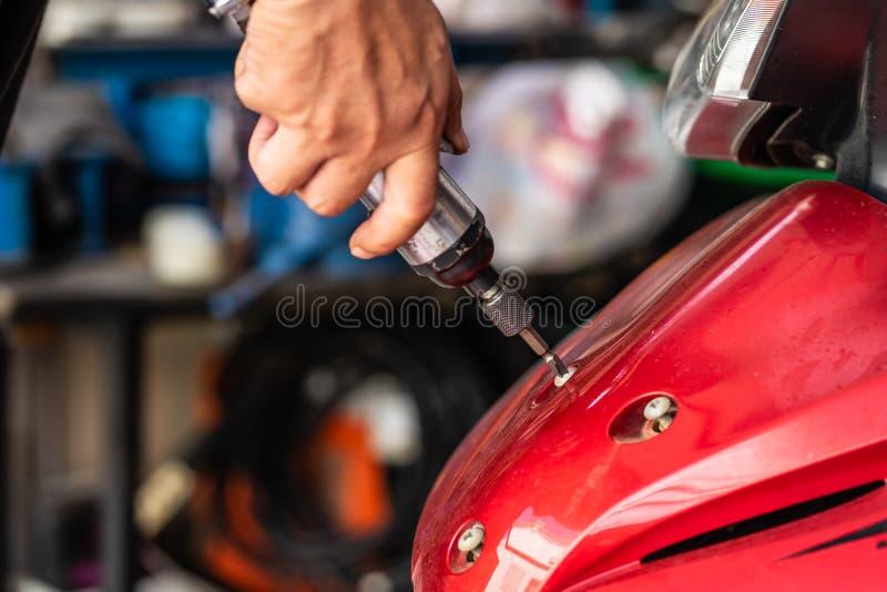 使用一把气动的螺丝刀修理或mainta的技工人 库存图片