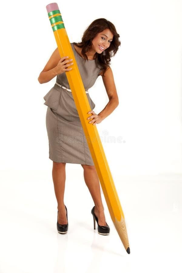 使用一支大铅笔的女商人写与 免版税库存照片
