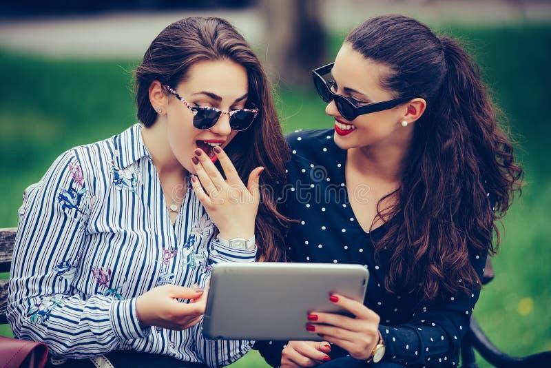 使用一数字平板电脑和笑的两个美丽的女性朋友 库存照片