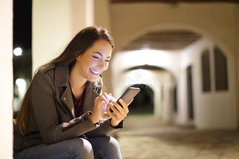 使用一智能手机的愉快的女性在街道的夜 库存图片
