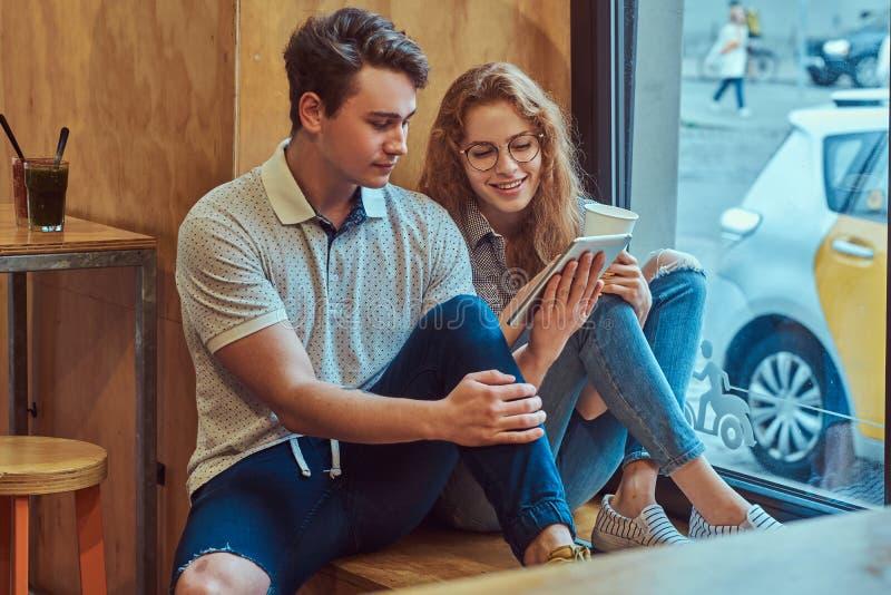 使用一种数字式片剂的两名愉快的年轻学生,当坐窗口基石在学院军用餐具在断裂期间时 图库摄影