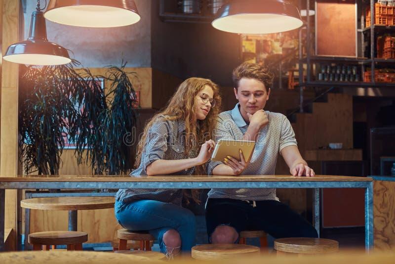 使用一种数字式片剂的体贴的年轻夫妇学生,当坐在桌在学院军用餐具在断裂期间时 免版税库存图片