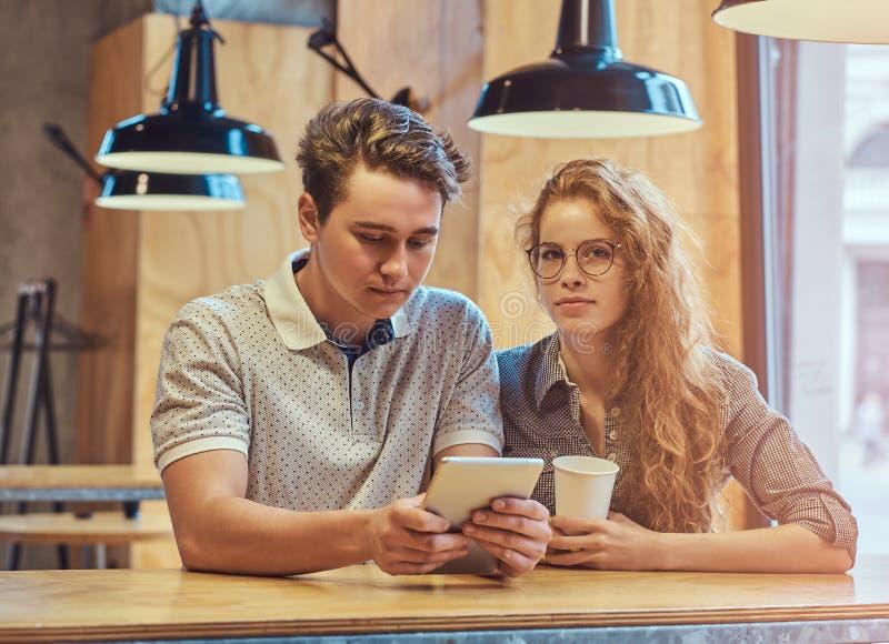 使用一种数字式片剂的体贴的年轻夫妇学生,当坐在桌在学院军用餐具在断裂期间时 库存图片