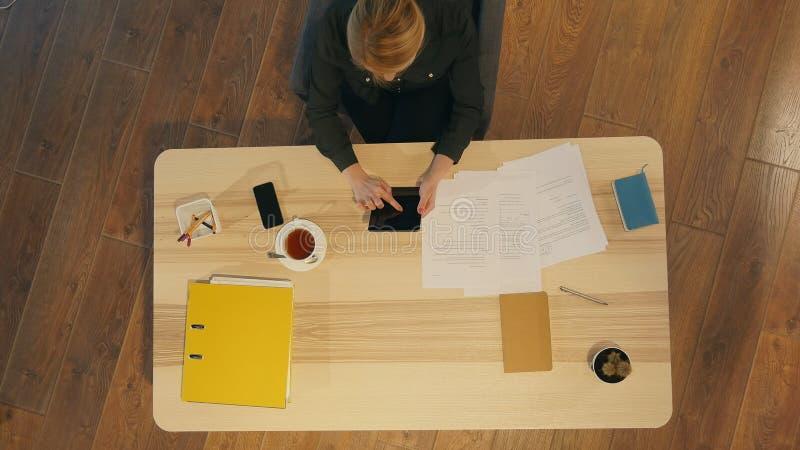 使用一种数字式片剂的可爱的女实业家whilesitting在窗口前面的书桌在办公室 库存照片