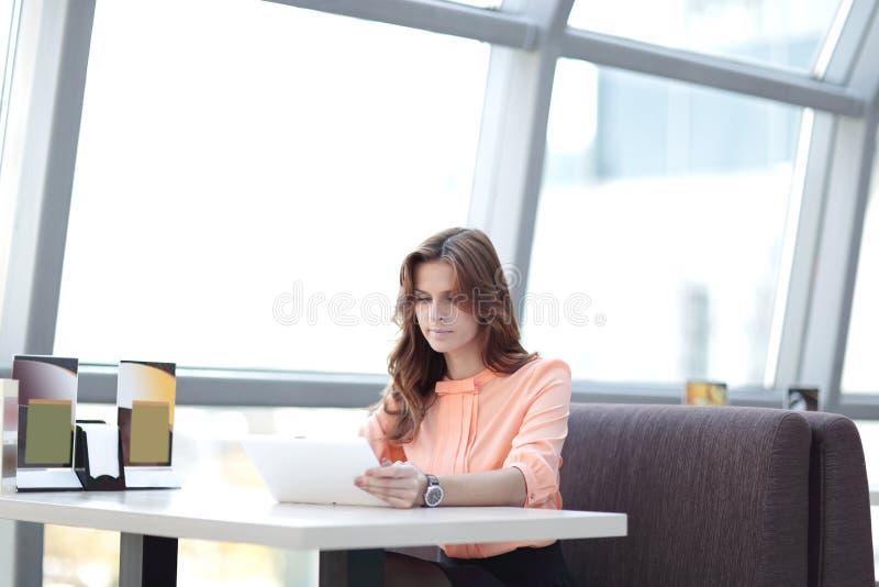 使用一种数字式片剂的妇女顾问在工作场所在办公室 免版税库存照片
