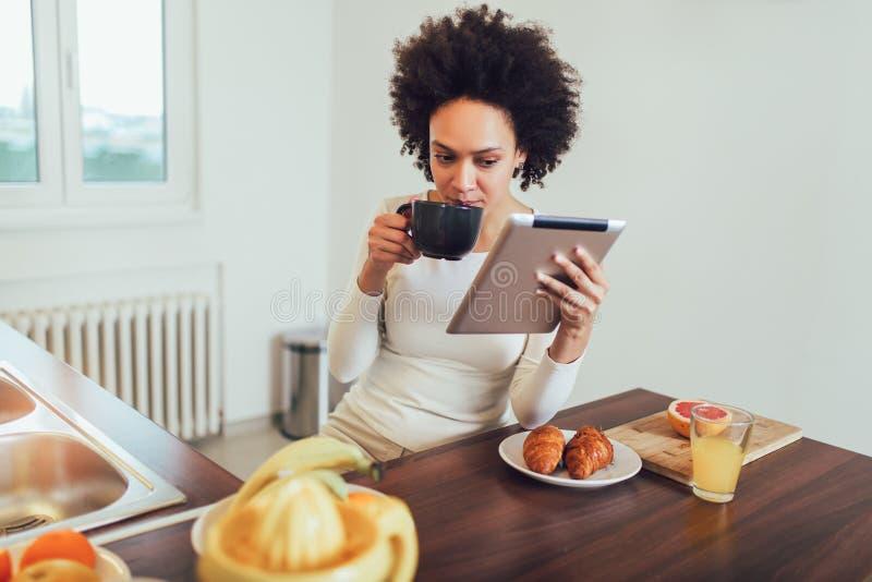 使用一种数字式片剂的少妇,当在家时放松 免版税图库摄影