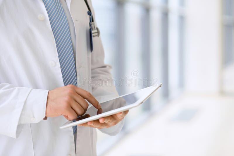 使用一种数字式片剂,手特写镜头的医生  背景弄脏了关心概念表面健康防护屏蔽的药片 库存图片