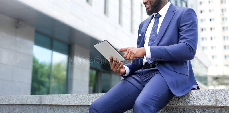 使用一种数字片剂的非洲商人特写镜头,当坐办公楼时 免版税库存图片