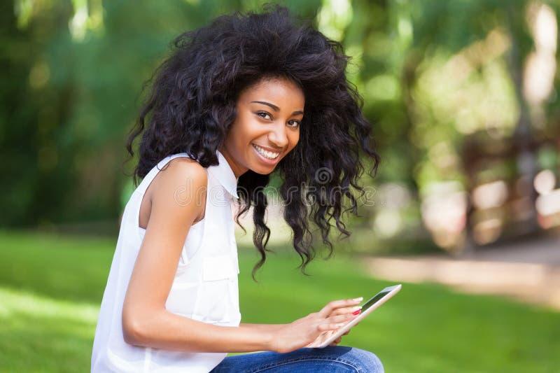 使用一种有触觉的片剂的一个少年黑人女孩的室外画象 免版税库存照片
