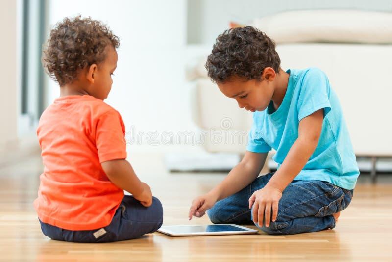 使用一种有触觉的片剂的非裔美国人的孩子的 免版税库存图片