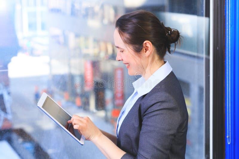 使用一种片剂,在窗口前面的美丽的女实业家在o 免版税库存图片