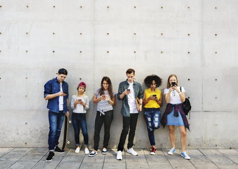 使用一起智能手机和ch,小组户外年轻成人 免版税库存图片