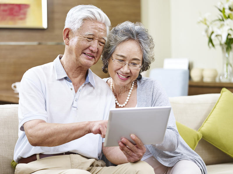 使用一起片剂计算机的资深亚洲夫妇 免版税库存照片