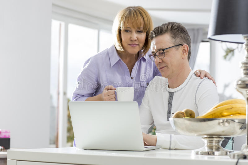 使用一起膝上型计算机的成熟夫妇在桌上在房子里 库存图片
