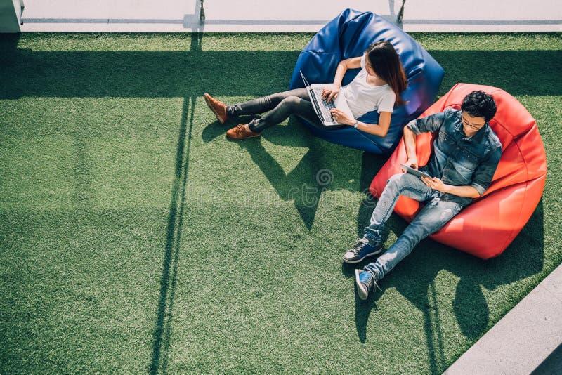 使用一起膝上型计算机笔记本和数字式片剂的亚洲夫妇在现代公园,坐辎重袋,与拷贝空间的顶视图 库存照片