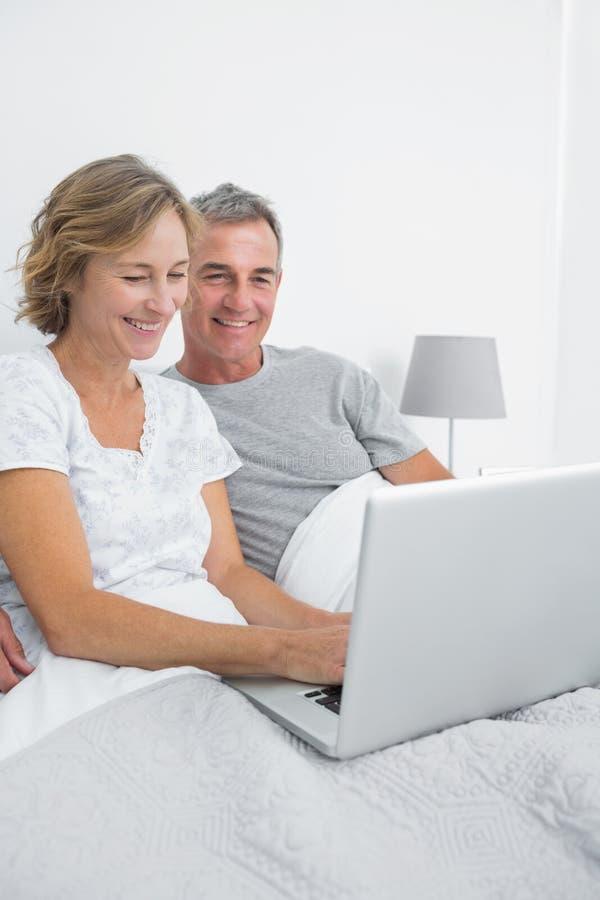 使用一起他们的膝上型计算机的快乐的夫妇在床上 库存照片