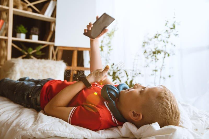 使用不同的小配件的小男孩在家 库存图片