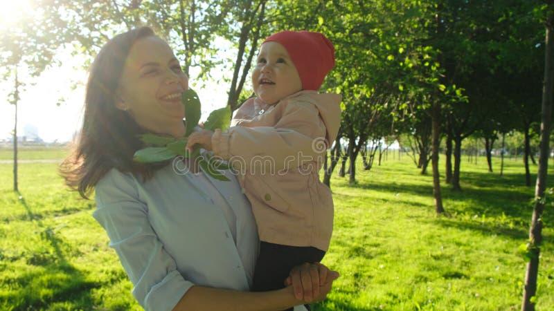 使用与一个分支的愉快的家庭在公园在日落 母亲抱胳膊的一个孩子户外 库存图片