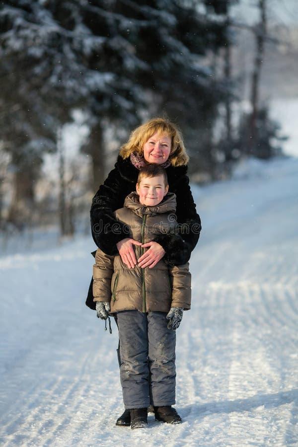 使用与一个小男孩的年轻女人在冬天公园 免版税库存照片
