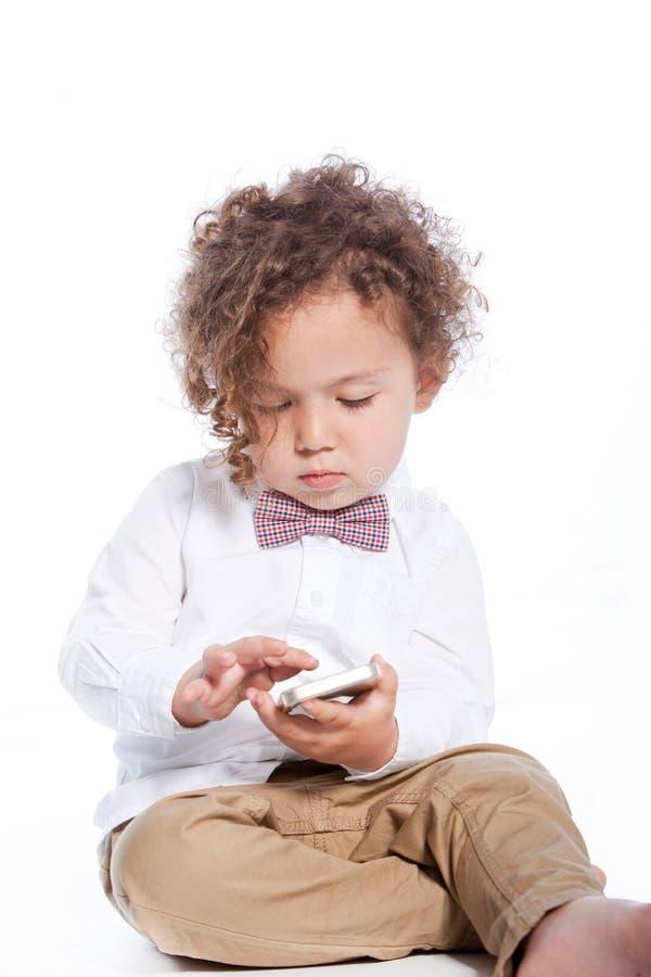 使用与一个手机的逗人喜爱的小男孩 库存照片
