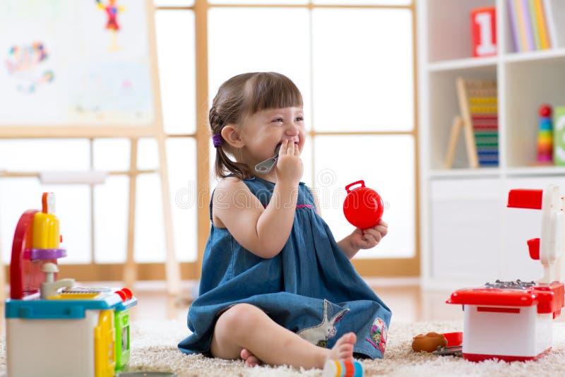 使用与一个玩具厨房的俏丽的儿童女孩在儿童居室 库存图片
