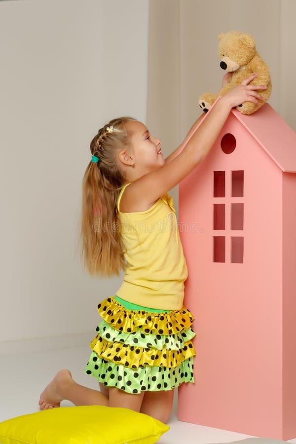 使用与一个玩具熊的女孩在玩具木房子里 免版税库存照片