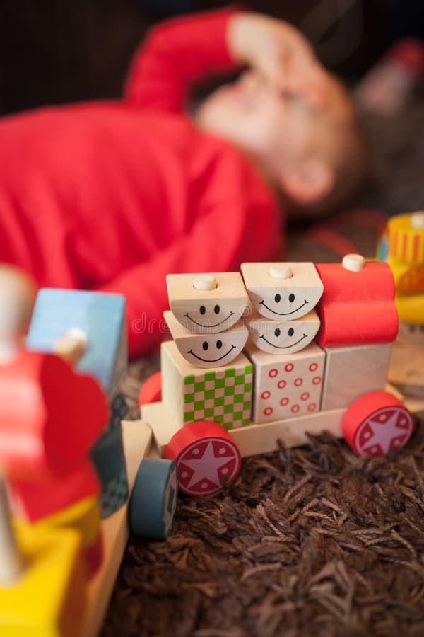使用与一列木玩具火车的疲乏的男孩 免版税图库摄影