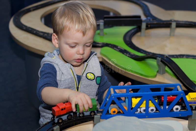 使用与一列玩具火车的逗人喜爱的小孩对于儿童集中 免版税库存照片