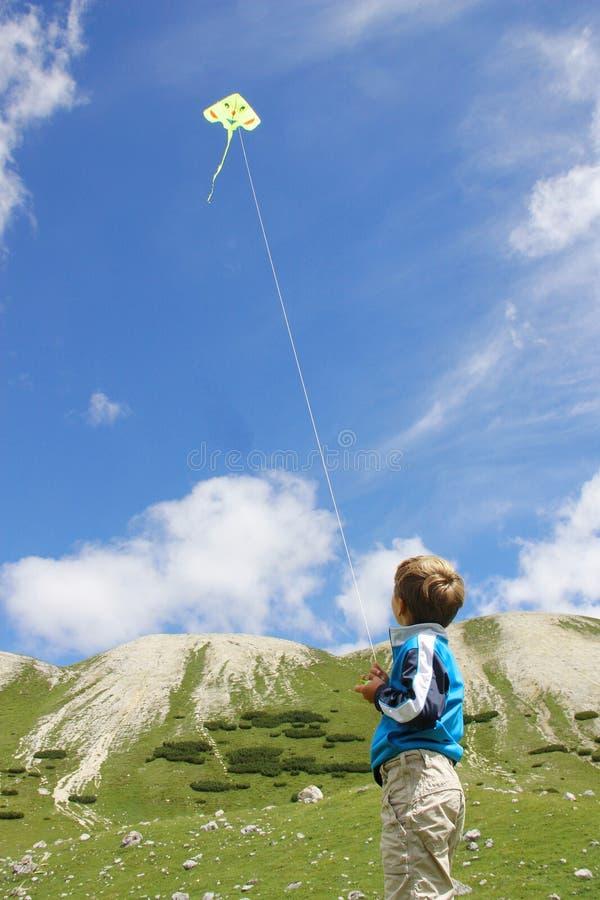 使用与一只黄色风筝的年轻男孩 免版税库存照片