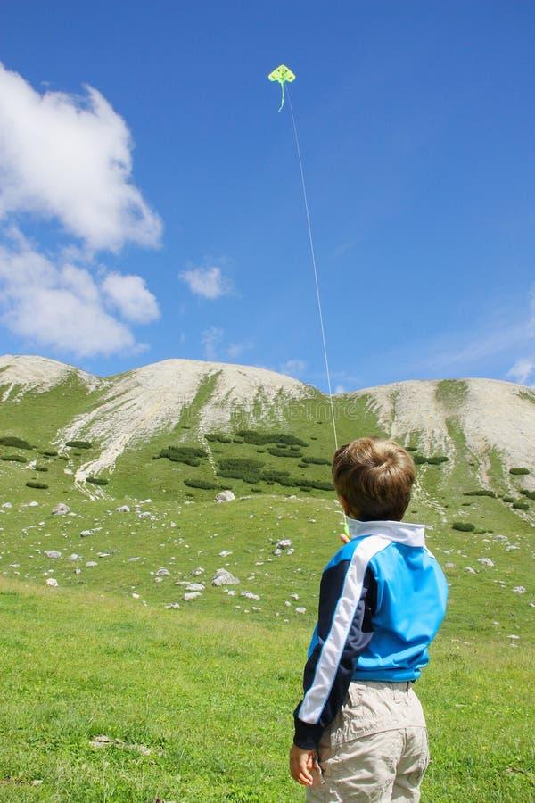 使用与一只黄色风筝的年轻男孩 图库摄影