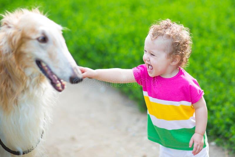 使用与一条大狗的愉快的笑的婴孩 免版税库存照片