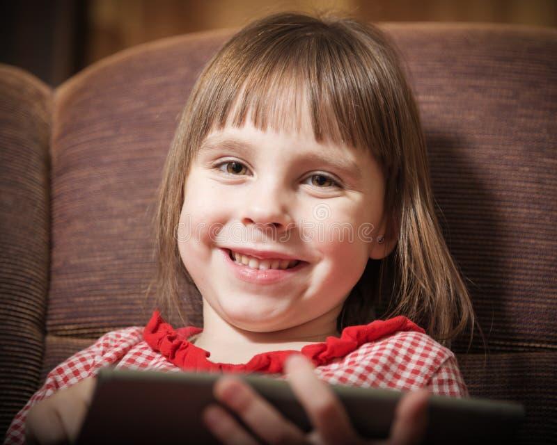 使用与一种现代数字式片剂的小女孩 免版税库存图片