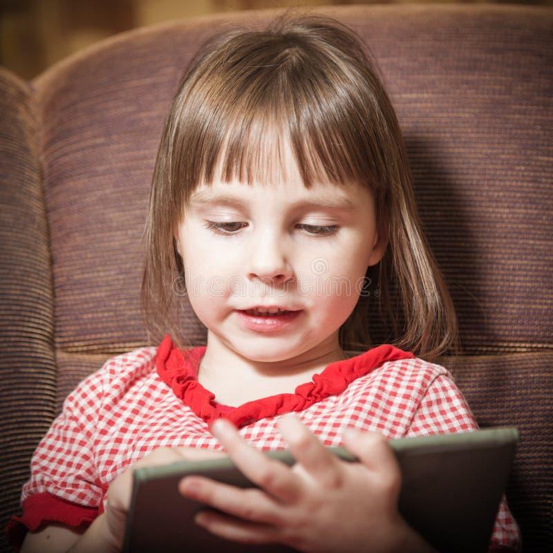 使用与一种现代数字式片剂的小女孩 库存照片