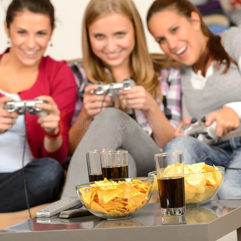 使用与电子游戏的微笑的十几岁的女孩 免版税库存照片