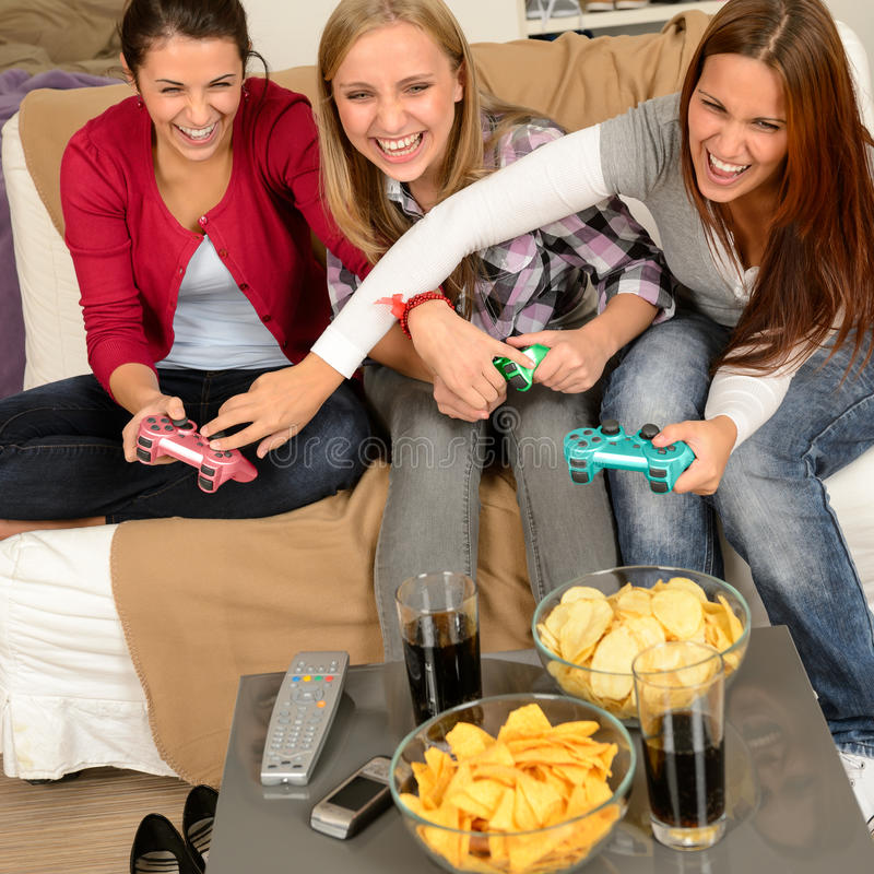 使用与电子游戏的笑的十几岁的女孩 免版税库存照片