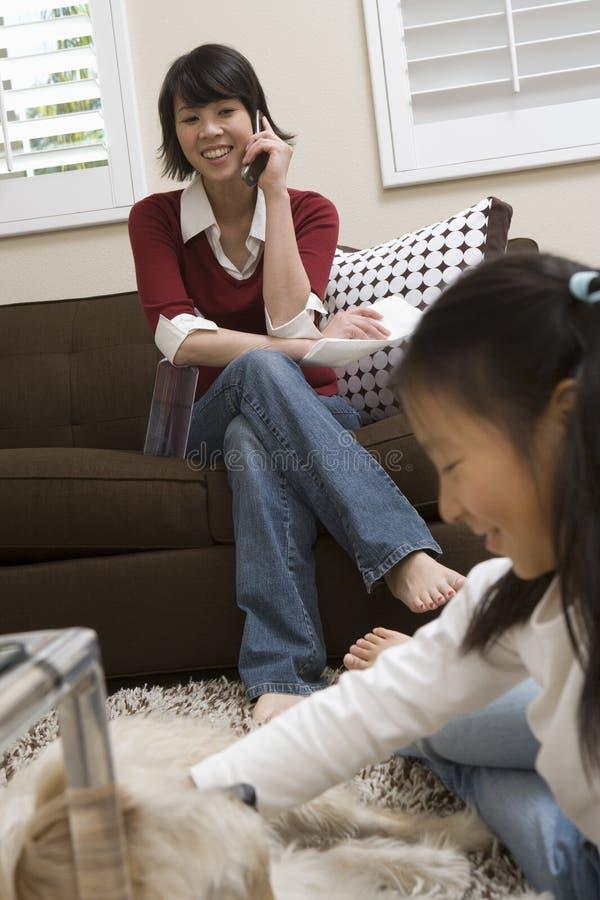 使用与与母亲的狗的女孩电话的 库存照片